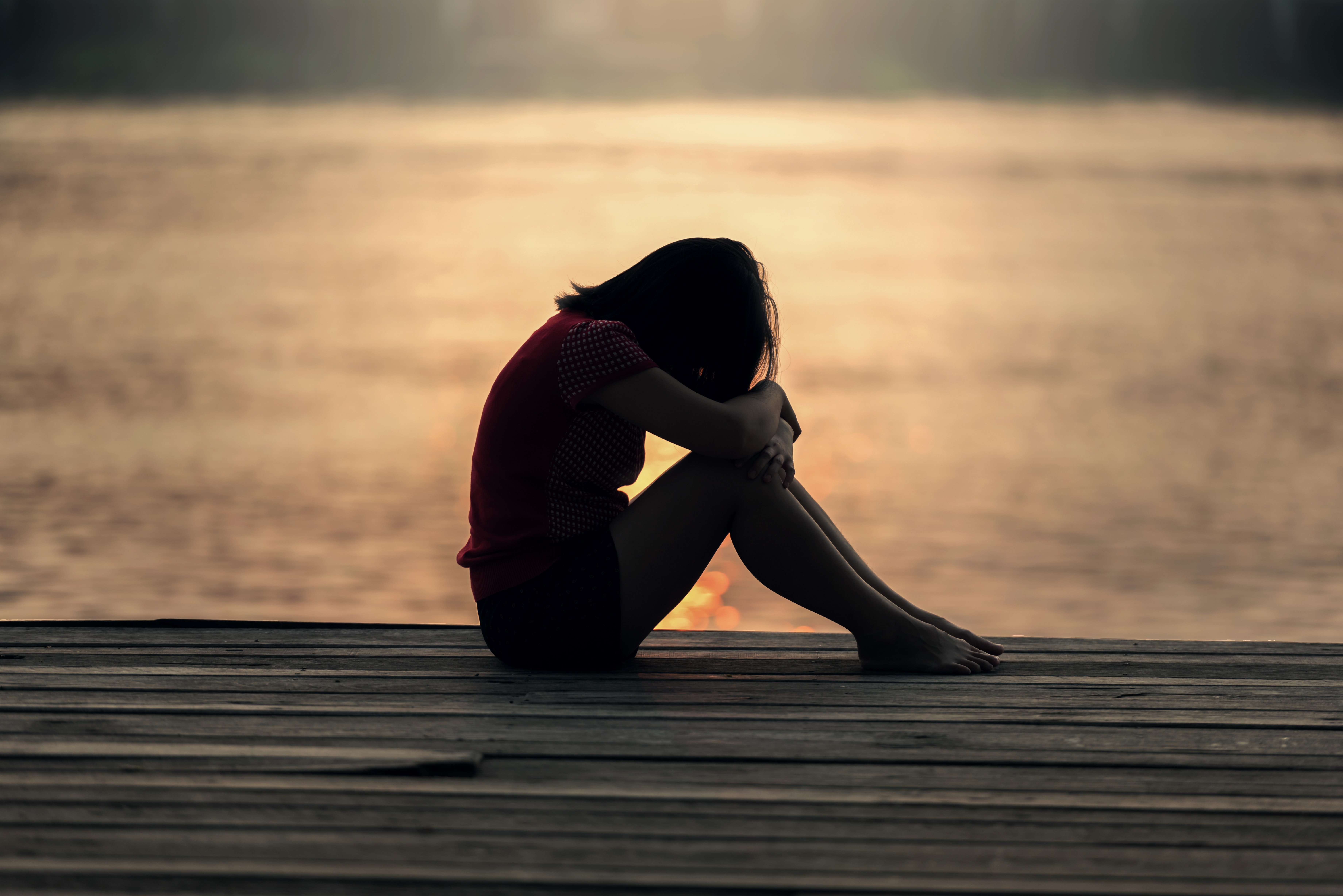 A girl sits on a dock with her head on knees feeling distressed. She has decided to pursue trauma therapy in Forest Hills, NY with trauma therapist Deborah Karnbad. You can also get online counseling with trauma therapy in New York too!
