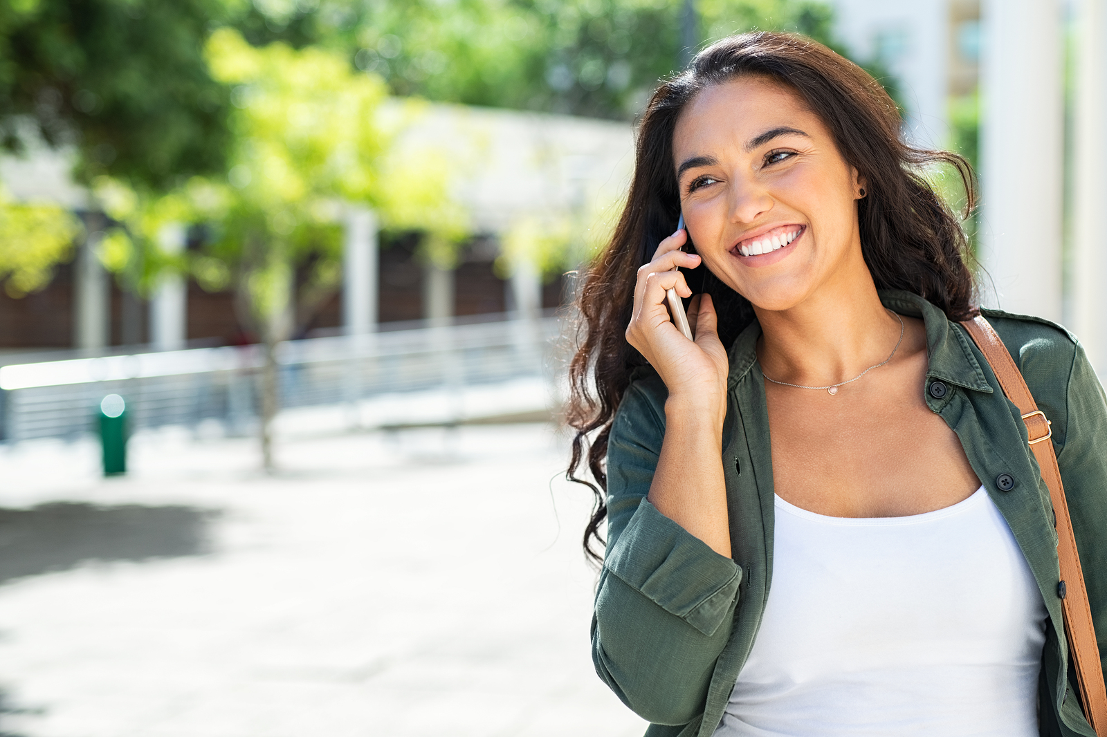 A girl smiles while talking on the on the phone. She is happy with her decision to begin trauma therapy in Forest Hills, NY with trauma therapist Deborah Karnbad.