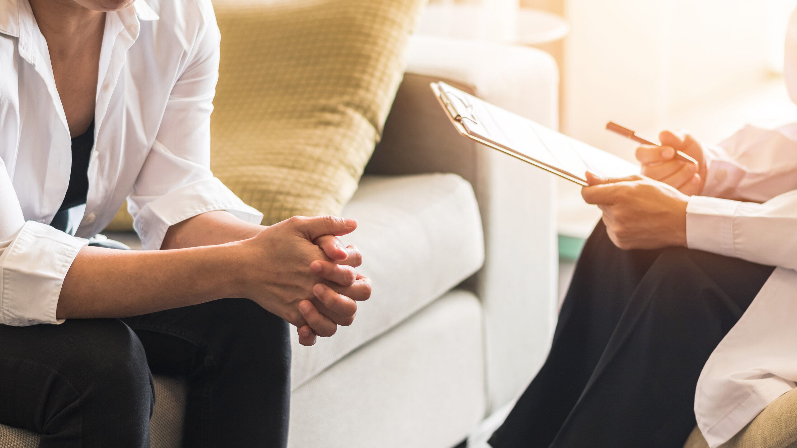 Two individuals sit in a room during a therapy session. They are in their first appointment for trauma therapy in Forest Hills, NY with trauma therapist Deborah Karnbad.