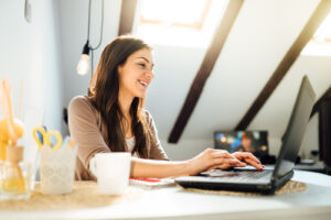 A woman smiles while using her laptop. She has started online therapy in New York for trauma therapy, couples counseling and counseling for divorce step parents with Deborah Karnbad.