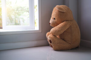 A stuffed bear sits next to the window, looking sad. This is an example of sadness is a common reason why people pursue online therapy in New York with Deborah Karnbad who specializes in trauma therapy in forest hills, ny and beyond..