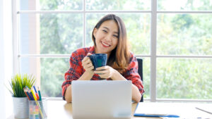 A woman smiles while using her laptop. She is happy with her decision to pursue online therapy for college students in New York with Deborah Karnbad who specializes in trauma therapy in forest hills, ny.