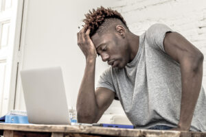 A male college student looks at his laptop, and appearing to feel overwhelmed. He is excited to start online therapy for college students in New York with Deborah Karnbad.