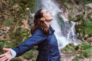 A girls stands in front of a waterfall with her arms extended behind her. She is feeling more calm after starting anxiety therapy in Forest Hills, NY with Deborah Karnbad.