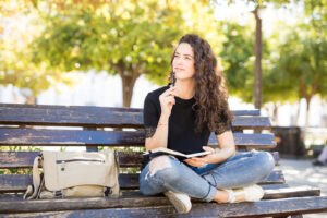 A girl sits on a bench. She is excited to start anxiety therapy in Forest Hills, NY with Deborah Karnbad.