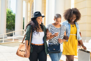 Three female college students walk while holding arms. They are happy with their decision to pursue online therapy for college students in New York with Deborah Karnbad.