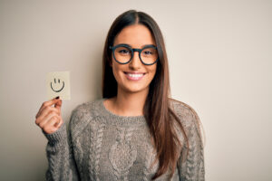 A girl smiling stands against a blank wall holding a piece of paper with a smiley face drawn on it. She is feeling much happier after beginning online therapy for college students in New York with Deborah Karnbad.
