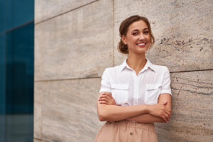 A woman smiles while leaning against a wall. She is feeling much happier since starting depression counseling in Long Island, NY with Deborah Karnbad.