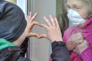 A child makes a heart with his fingers on a window. The reflects concepts of anxiety and depression in forest hills, ny discussed in online therapy in New York with Deborah Karnbad, 11375.