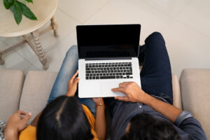A couple sits next to each other using a laptop. They are starting online marriage counseling in Forest Hills, NY with Deborah Karnbad and in online therapy in New York 11375