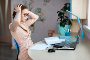 A girl sits at a desk looking frustrated. She is looking forward to starting online marriage counseling in New York with Deborah Karnbad 11375.