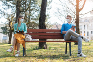 A couple sits away from each other on a bench. They are looking forward to starting online marriage counseling in New York with Deborah Karnbad 11375.
