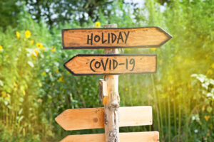 """A wooden sign reads """"holiday"""" and """"COVID."""" You can discuss your concerns about anxiety and depression with online therapy in New York with Deborah Karnbad 11375. Get depression counseling, anxiety treatment, trauma therapy and more here."""