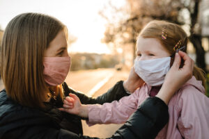 A mom helps her daughter put on a mask. This reflects concepts discussed in an online support group in New York with Deborah Karnbad. You can get online therapy in New York for frustrated women, overwhelmed moms and more here!